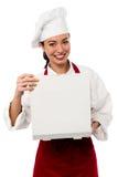 Caja femenina sonriente de la pizza de la abertura del cocinero foto de archivo libre de regalías