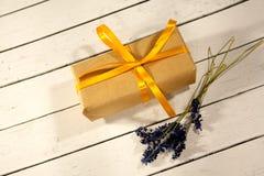 Caja festiva del regalo con las flores de la lavanda y cinta amarilla en pizca imagenes de archivo