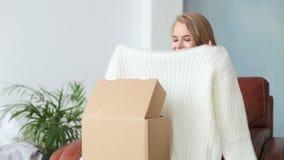Caja hermosa de la abertura de la mujer joven con el paquete en casa almacen de metraje de vídeo