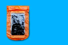 Caja impermeable anaranjada del tel?fono m?vil con las gotitas de agua aisladas en fondo azul Bolso de la cerradura de la cremall foto de archivo