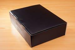 Caja negra misteriosa en el fondo de madera Imagen de archivo libre de regalías