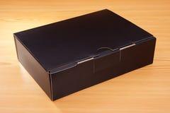 Caja negra misteriosa en el fondo de madera Fotos de archivo libres de regalías