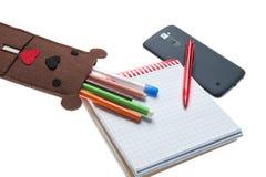 Caja para las plumas y teléfono con el cuaderno imágenes de archivo libres de regalías