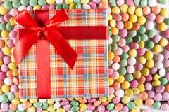 Caja plana de la endecha con el arco rojo sobre los caramelos redondos coloridos Fotografía de archivo libre de regalías