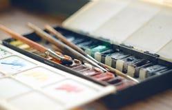 Caja plegable con las pinturas de la acuarela en cubetas y cepillos fotos de archivo libres de regalías