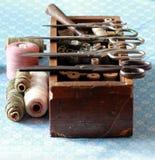 Caja que hace punto con muchas herramientas y tijeras del hilo Foto de archivo