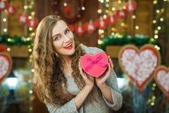 Caja que se sostiene rubia hermosa bajo la forma de corazón en manos Foto de archivo