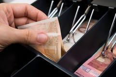 Caja registradora de Person Hands With Money Over Fotografía de archivo