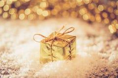 Caja retra del oro de la Navidad en la nieve con la luz de oro del fondo Fotos de archivo