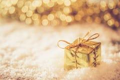 Caja retra del oro de la Navidad en la nieve con la luz de oro del fondo Imagen de archivo