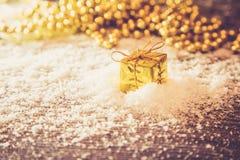 Caja retra del oro de la Navidad en la nieve con la luz de oro del fondo Imagenes de archivo