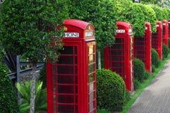 Caja roja BRITÁNICA tradicional del teléfono del viejo estilo en jardín imagenes de archivo