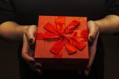 Caja roja con un arco a disposición, regalo imagenes de archivo