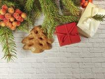 Caja roja con un arco en un fondo del ladrillo, pan de jengibre, galletas de la rama de la Navidad Imagenes de archivo