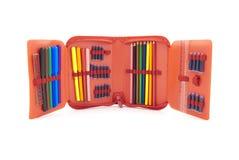 Caja roja con un conjunto de plumas y de lápices de la extremidad Fotos de archivo libres de regalías
