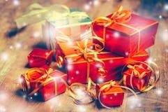 Caja roja del regalo del fondo del Año Nuevo con los presentes en el tablero de madera con nieve Imagen de archivo libre de regalías