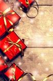 Caja roja del regalo del fondo del Año Nuevo con los presentes en el tablero de madera con nieve Foto de archivo libre de regalías