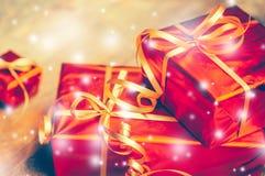 Caja roja del regalo del fondo del Año Nuevo con los presentes en el tablero de madera con nieve Fotos de archivo libres de regalías