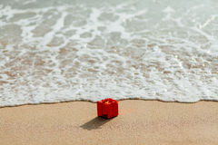Caja roja del regalo en la playa Fotografía de archivo libre de regalías