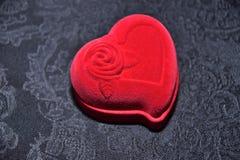 Caja roja para los anillos bajo la forma de corazón en un fondo negro Fotografía de archivo