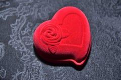 Caja roja para los anillos bajo la forma de corazón en un fondo negro Imagen de archivo libre de regalías