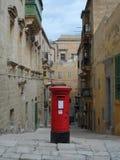 Caja roja tradicional de los posts en calle estrecha en Malta Fotografía de archivo