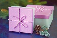 Caja rosada de los regalos de la Navidad en fondo azul Ramificación spruce verde Foto de archivo libre de regalías