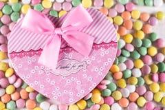 Caja rosada del corazón con el arco sobre los caramelos redondos coloridos Fotos de archivo