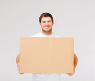 Caja sonriente del cartón del hombre que lleva Foto de archivo