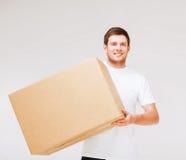 Caja sonriente del cartón del hombre que lleva Imagen de archivo libre de regalías