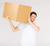 Caja sonriente del cartón del hombre que lleva Fotos de archivo