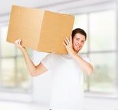 Caja sonriente del cartón del hombre que lleva Imágenes de archivo libres de regalías