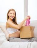 Caja sonriente del paquete de la abertura de la mujer embarazada Imágenes de archivo libres de regalías