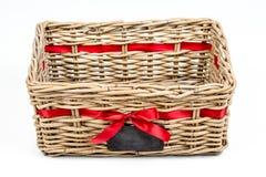Caja tejida del rectángulo, cesta con la cinta roja de la cinta de satén y pequeña pizarra Fotos de archivo libres de regalías