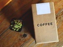 Caja y cactus del café del papel de Kraft en la tabla de madera del vintage Fotos de archivo libres de regalías