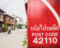 Caja y moto rojas de los posts en Chiang Khan, Loei, Tailandia imagenes de archivo