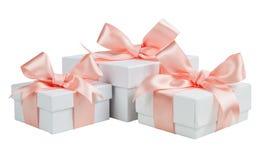 Cajas blancas con las cintas rosadas aisladas en el fondo blanco Foto de archivo libre de regalías