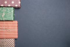 Cajas coloridas con los regalos en un fondo negro foto de archivo