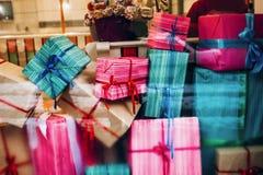 Cajas coloridas hermosas de los presentes en ventana regalos de la Navidad adentro Fotos de archivo libres de regalías