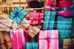 Cajas coloridas hermosas de los presentes en ventana regalos de la Navidad adentro Imagen de archivo