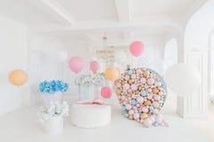 Cajas con flores y un pudrinitsa grande con las bolas y globos en el sitio adornado para la fiesta de cumpleaños Imagen de archivo libre de regalías