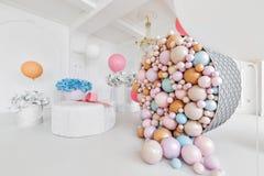 Cajas con flores y un pudrinitsa grande con las bolas y globos en el sitio adornado para la fiesta de cumpleaños Fotos de archivo libres de regalías