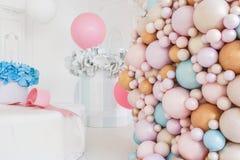 Cajas con flores y un pudrinitsa grande con las bolas y globos en el sitio adornado para la fiesta de cumpleaños Imágenes de archivo libres de regalías