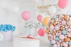 Cajas con flores y un pudrinitsa grande con las bolas y globos en el sitio adornado para la fiesta de cumpleaños Fotografía de archivo libre de regalías