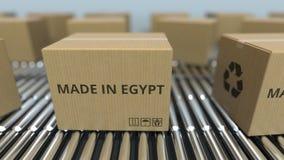 Cajas con HECHO EN el texto de EGIPTO en transportador de rodillo Las mercancías egipcias relacionaron la representación 3D ilustración del vector