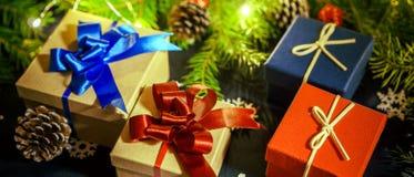 Cajas con los regalos en el fondo de las ramas, de los conos y de las guirnaldas del ABETO imagenes de archivo