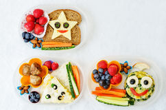 Cajas de almuerzo escolar para los niños con la comida bajo la forma de caras divertidas Imagenes de archivo