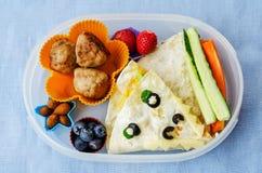 Cajas de almuerzo escolar para los niños con la comida bajo la forma de caras divertidas Foto de archivo