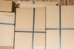 Cajas de cartón apiladas en un almacén fotos de archivo