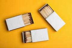 Cajas de cartón con los partidos en el fondo del color, endecha plana fotos de archivo
